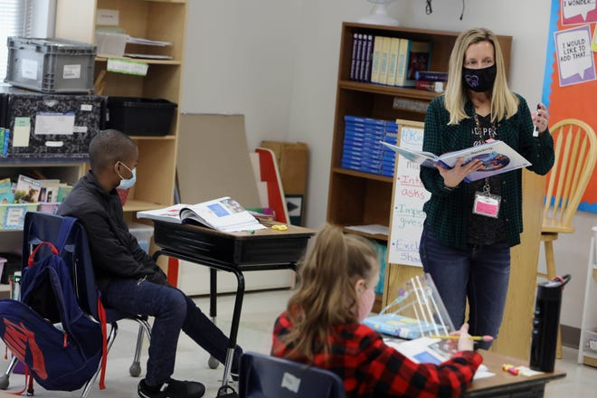 Elizabeth Junker, a fourth-grade teacher, goes over a reading lesson with her students Dec. 14 at Grimes Elementary School. Burlington students will return to 100% in-person instruction Feb. 8.