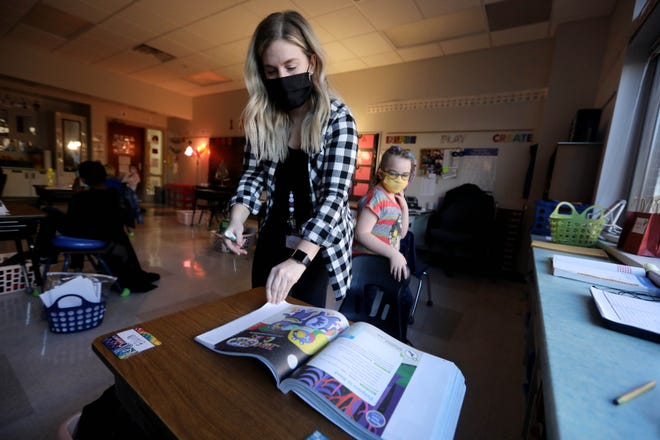 Suzi Grover, a third-grade teacher, opens Elora Bowen's reading workbook to the correct page Monday at Grimes Elementary School. After just more than a month of full remote learning, Burlington teachers and students returned to their classrooms Monday as the district resumed its hybrid learning model.