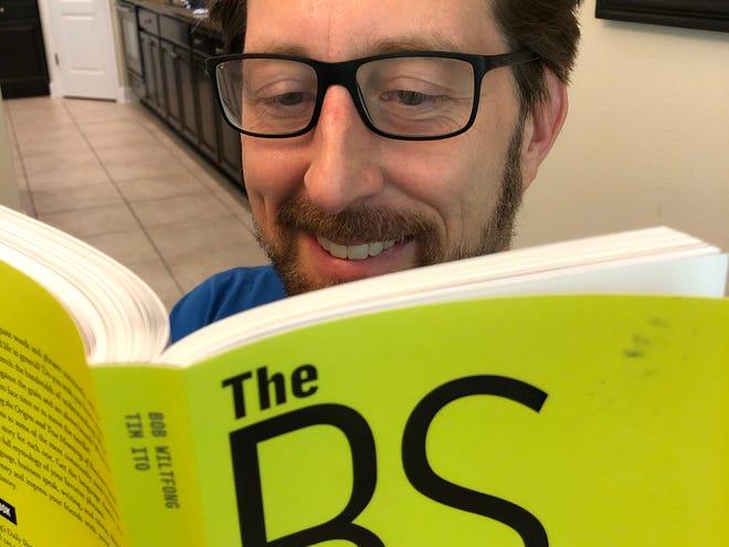 "Bob Wiltfong reading a copy of his book, ""The BS Dictionary."""