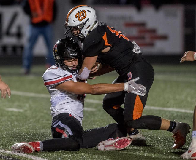 Metamora's Ryne Begole, left, gets ahold of Washington ballcarrier Jacob Sollberger in the second half Friday, Oct. 18, 2019 in Washington.