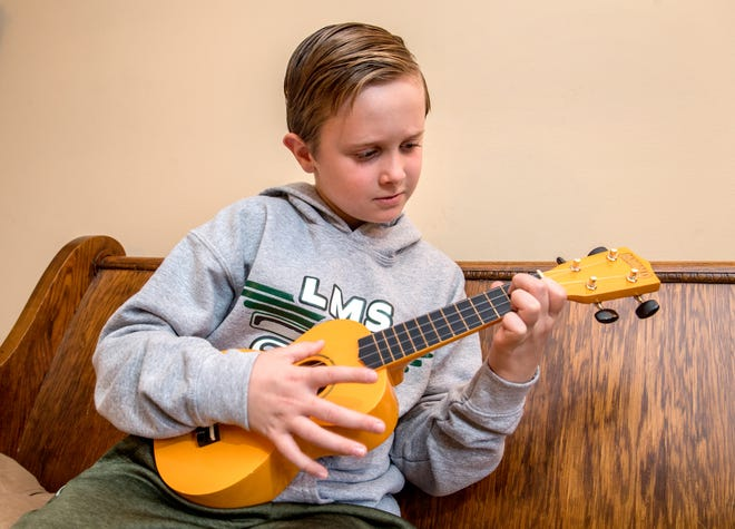 Cole Lystila, 11, strums away on his ukulele at his North Peoria home. The Linbergh Middle School fifth-grader has been able to continue his musical education despite COVID-19 restrictions thanks to teacher Atsuko Masuyama and a closet full of ukuleles.