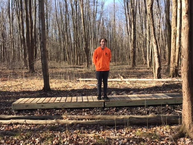 Logan Gerstenfeld stands on one of the footbridges he helped construct for the Buttonbush Trace trail at Liberty Park.
