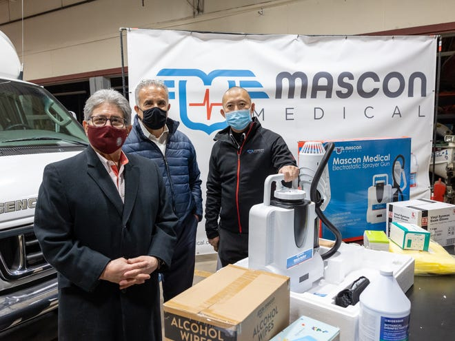 John Chen, right, global president and CEO of Mascon, Inc. in Woburn, presents Leominster Mayor Dean Mazzarella, center, and Fitchburg Mayor Stephen DiNatale with more than 250,000 donated masks, gowns, face shields, goggles, hand sanitizing wipes, and electrostatic sprayers Tuesday, Dec. 8 at the Leominster Office of Emergency Management.