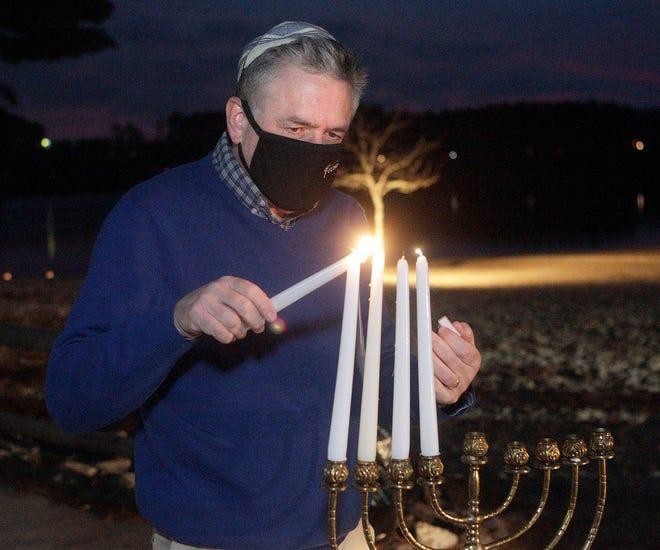 Rabbi Tom Alpert of Temple Etz Chaim lights the menorah at the Chilson Beach Recreation Area for the Hanukkah celebration in Franklin, Dec. 13.