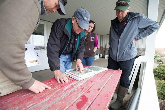 Don Jensen, at center, is seen at his Lawnhurst Farms in the Ontario County town of Seneca in 2018. From left is Tucker Kautz, Ontario County Soil and Water senior district technician, Megan Webster, Ontario SWCD manager, and  Karl Czymmek, senior extension associate with Cornell.
