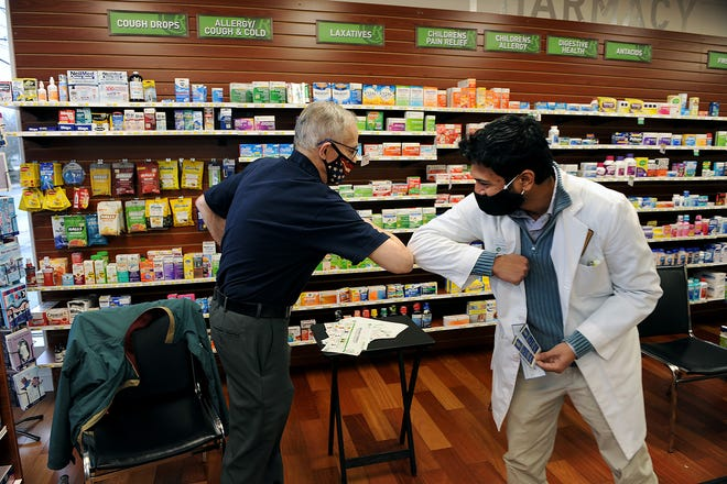 Charles River Rotary Club of Framingham and Natick member  Tom Daly, left, elbow bumps MetroWest Pharmacy Pharmacist Shivang Patel after presenting him a check, Dec. 14, 2020.
