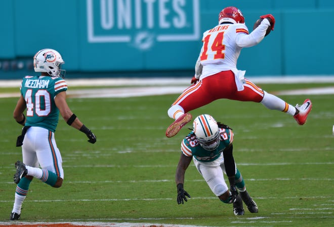 Chiefs receiver Sammy Watkins hurdles Dolphins safety Bobby McCain as Nik Needham looks on in December.