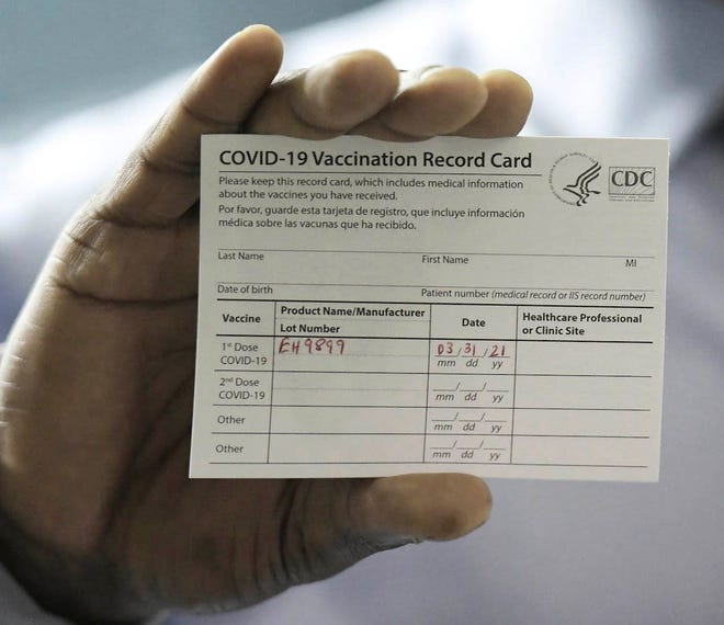 Dr. Leon Haley Jr., CEO of UF Health Jacksonville, shows his COVID-19 vaccination record card shortly before he received the first injection of the COVID-19 vaccine.