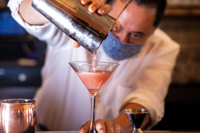 A bartender mixes a drink during an event at Almond Palm Beach for author Jules Aron's new cocktail book, Dec. 8.