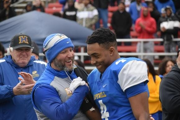 Hopewell head football coach Ricky Irby (left) congratulates running back TreVeyon Henderson (No. 4, right) during Hopewell's 35-7 win over Lord Botetourt in the VHSL Class 3 State Championship game in 2019.