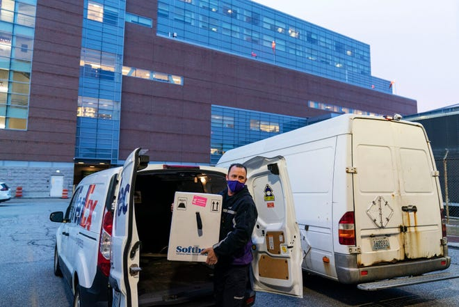 A FedEx driver delivers a box containing the Pfizer-BioNTech COVID-19 vaccine to Rhode Island Hospital in Providence, R.I., Monday, Dec. 14, 2020.