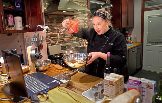 Emily Larsen prepares a lobster for her lobster bisque as she teaches a remote class on winter soups