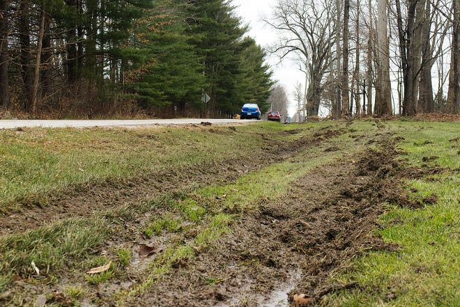 Tire tracks run across a ditch and through a portion of a Peck Road front yard leading up to the crash site.
