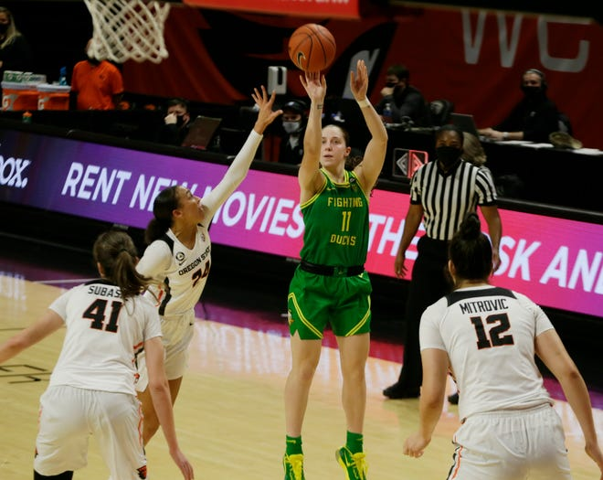 Oregon's Taylor Mikesell, center, shots against Oregon State during the second half.