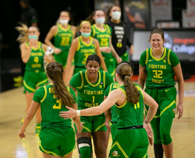 Oregon players celebrate their halftime lead against Oregon State in Corvallis on Sunday.