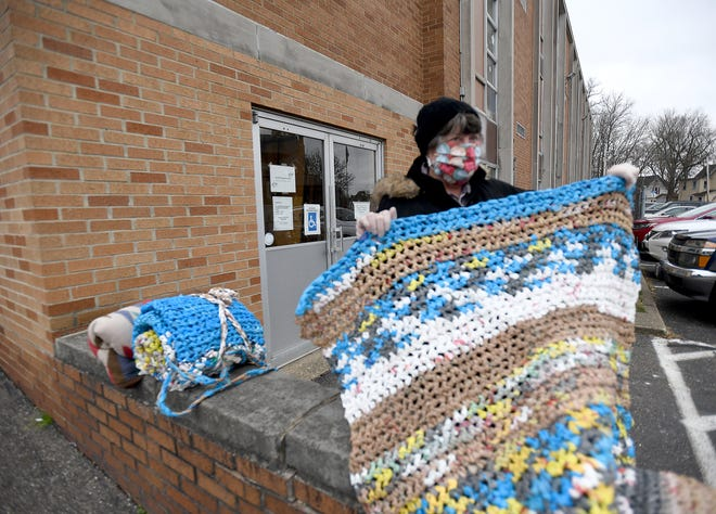Patti Crookston, a resident of Kroft Commons at Chapel Hill Community in Canal Fulton, shows off a sleeping mat made from plastic grocery bags. The mats are being distributed to the homeless at St. Joseph Catholic Church's soup kitchen.