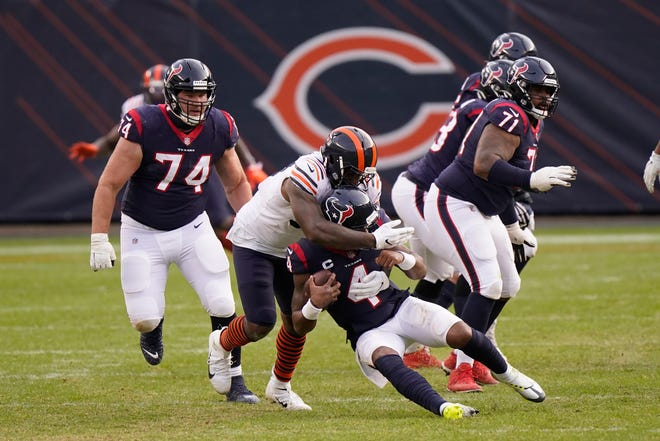 Houston Texans' Deshaun Watson (4) is sacked by Chicago Bears' Mario Edwards (97) during the second half of an NFL football game, Sunday, Dec. 13, 2020, in Chicago.
