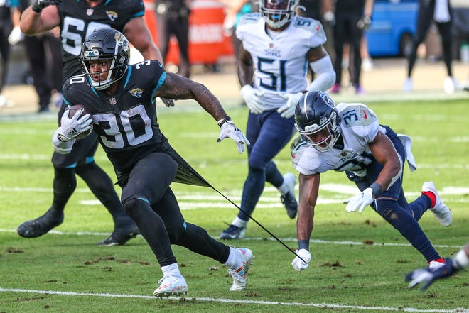 Tennessee Titans safety Kevin Byard (31), right, tears Jacksonville Jaguars running back James Robinson's (30) jersey during a second-half run Sunday, Dec. 13, 2020, in Jacksonville, Fla. Titans won 31-10