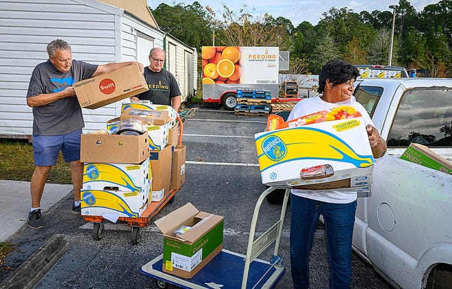 George Wright and Tom Wallace help SEA Community Center food bank manager Malinda Peeples load food onto the back of her truck on Monday, Dec. 14, 2020, behind the Family Worship Center's food pantry in St. Augustine.