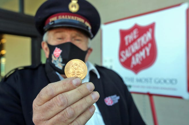 Les Ashby holds the gold coin that was anonymously dropped in a Salvation Army kettle outside Hobby Lobby of Shelby.