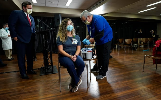 Florida Gov. Ron DeSantis watches as nurse Vanessa Arroyo, seated, prepares to get a Pfizer COVID-19 vaccine shot from nurse Rafael Martinez during a news conference Monday at Tampa General Hospital, which was one of the first hospitals in Florida to get the vaccine.