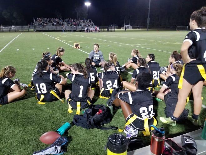 Richmond Hill head flag football coach Tony Dragon talks to the team during halftime of a game this season.