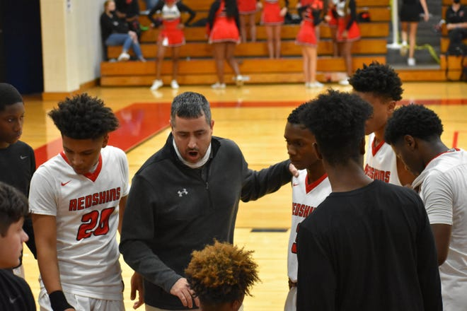 Bryan County boys basketball coach Brent Anderson addresses the team during a timeout.