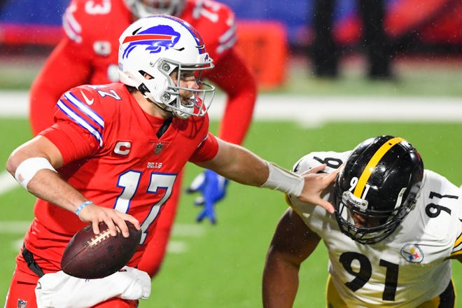 Bills quarterback Josh Allen, left, keeps Steelers defensive end Stephon Tuitt at arm's length while running with the ball during the second quarter Sunday night.
