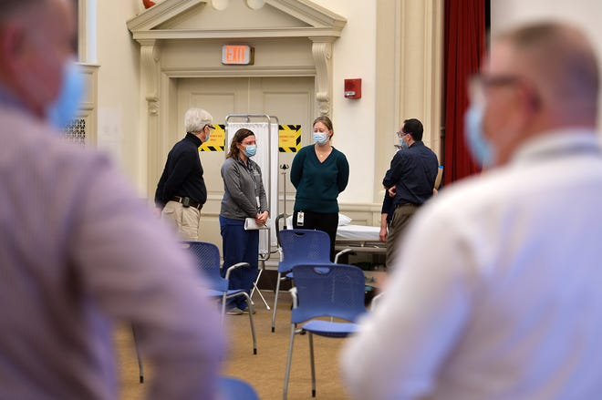 Elizabeth Radigan, center, director of clinical pharmacy services, talks with others about the vaccination process that will begin on Dec. 22 at the Knowles Hall location at UMass Memorial Medical Center off Belmont Street in Worcester.