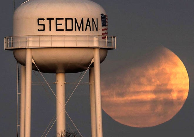 The partially eclipsed moon sets behind the Stedman water tower in this January 31, 2018, photo. A similar eclipse with similar timing will happen on the morning of May 26, when the partially eclipsed moon sets in the west at dawn.