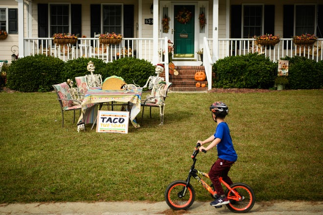 A neighborhood boy rides a bike past a Halloween display on Jacobs Creek Circle in Fayetteville in October 2020.