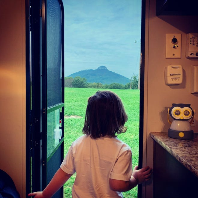 Teagan Holland-Criste opens the door of her family's camper for a view of Pilot Mountain from Jomeokee Campground in Pinnacle in fall 2020.