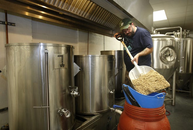Bo Hicks shovels grain into a barrel at the Druid City Brewing Co. in this  June 26, 2013, file photo. [Staff file photo]