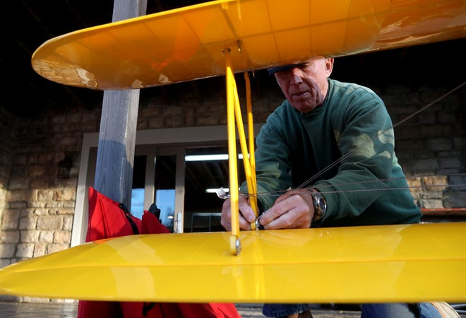 Mike Barbee, a Westerville Model Aeronautics Association member, attaches the wings on a model World War II-era radio-controlled biplane Dec. 10 at his home in Delaware. The WMAA has more than 100 members who fly radio-controlled aircrafts, with many of their events held at Dinneen RC Field near Alum Creek Lake in Galena.