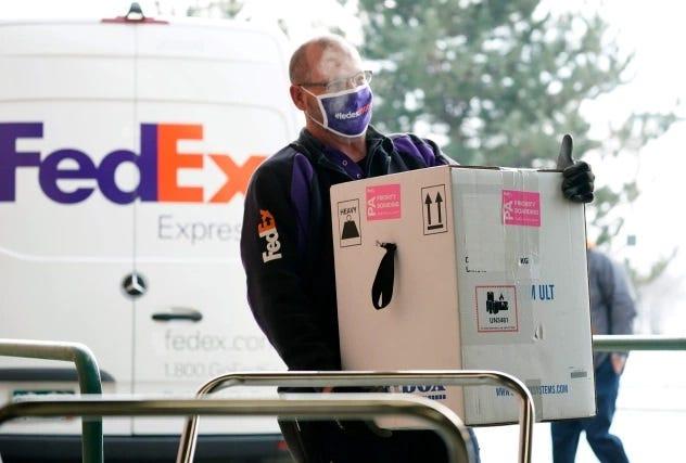 A FedEx driver carries a box.