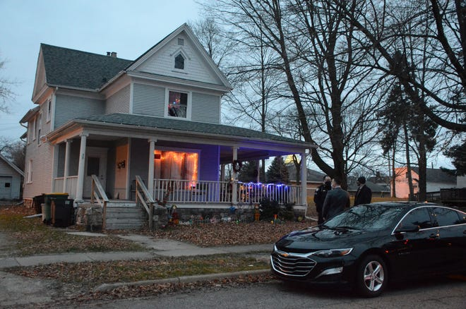 Battle Creek police confer outside 38 College St. Monday where a 61-year-old man died.