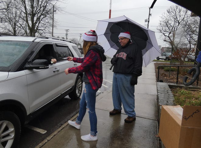 Emma Crawford and Randy Fischer help a customer during a drive-thru ornament sale on Saturday.