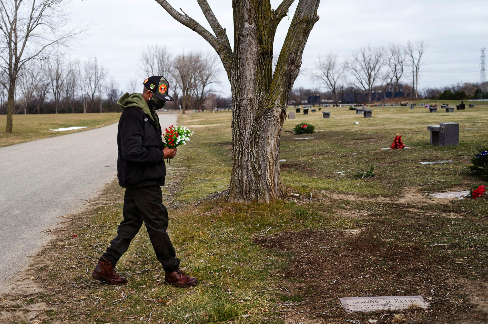 David Adaway places flowers on his mother's grave at the Detroit Memorial Park on Sunday, Dec. 6, 2020, in Redford Township.