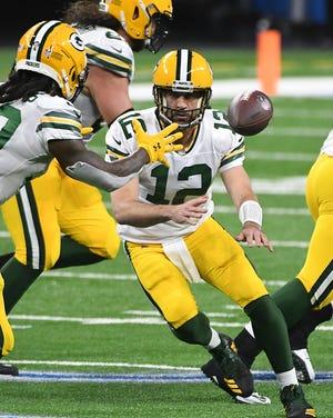 Aaron Rodgers dari Packers mengoper bola kembali untuk berlari kembali Jamaal Williams di kuarter ketiga.