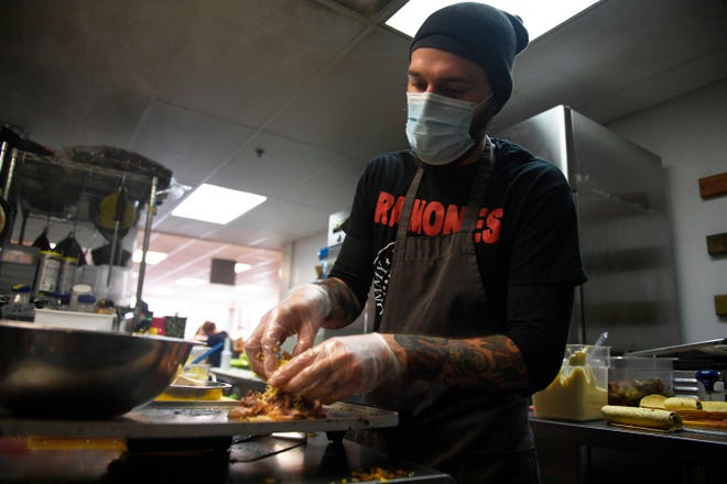 Head Chef Austin Brown prepares a RosemaryHam Roast Beef Havarti Sandwich at the ComeUnity Cafe, in Jackson, Tenn., Friday, December 11, 2020. The Cafe celebrates their 7th anniversary since they opened their doors to the public.
