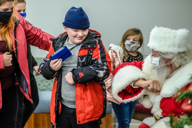 With some gentle urging from his mother, Alanson Robinson, left, and siblings Evan and Abby, Lance Robinson, 11, smiles and elbow bumps Santa at the Williamston United Methodist Church during a low sensory-stimulating event for children with disabilities Sunday, Dec. 13, 2020.