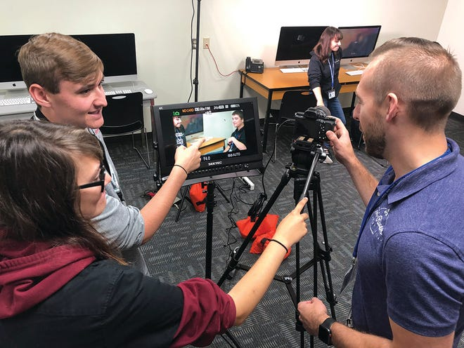 Interactive Media Instructor Josh Ebert, right, works with students in his lab. The program is one of 16 featured in Tri-Rivers' new virtual video.
