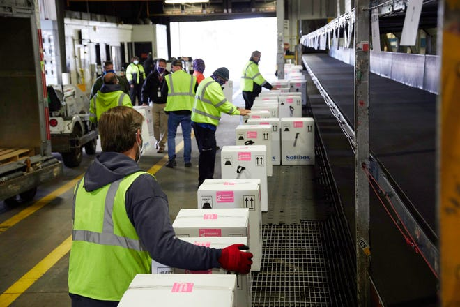 FedEx Express World Hub employees handle packages containing doses of the COVID-19 vaccine developed by Pfizer and BioNTech on Sunday in Memphis.
