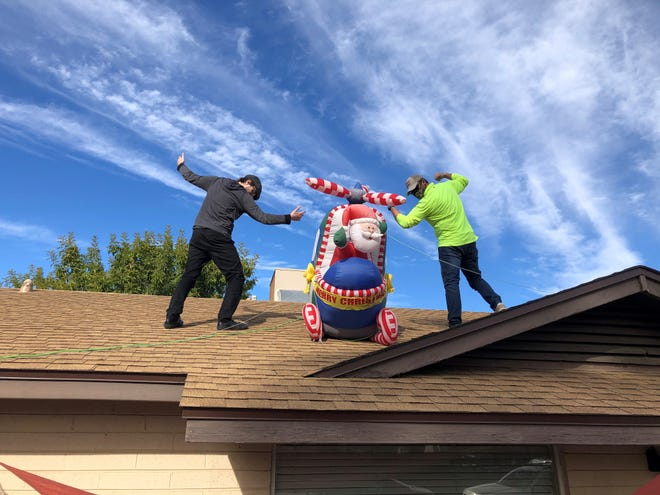 Sawyer Bland and Aaron Carriere got the inflatable Santa up on the roof again this year without major mishaps.