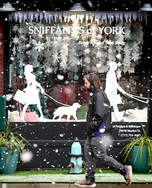 Florian Schmid of York City walks past a snowy window display for Sniffany's of York, a pet spa and boutique on West Market Street in the city, during a snow squall Monday, Dec. 14, 2020. Schimd was heading to the post office. York County and the region were under a winter weather advisory Monday. Bill Kalina photo