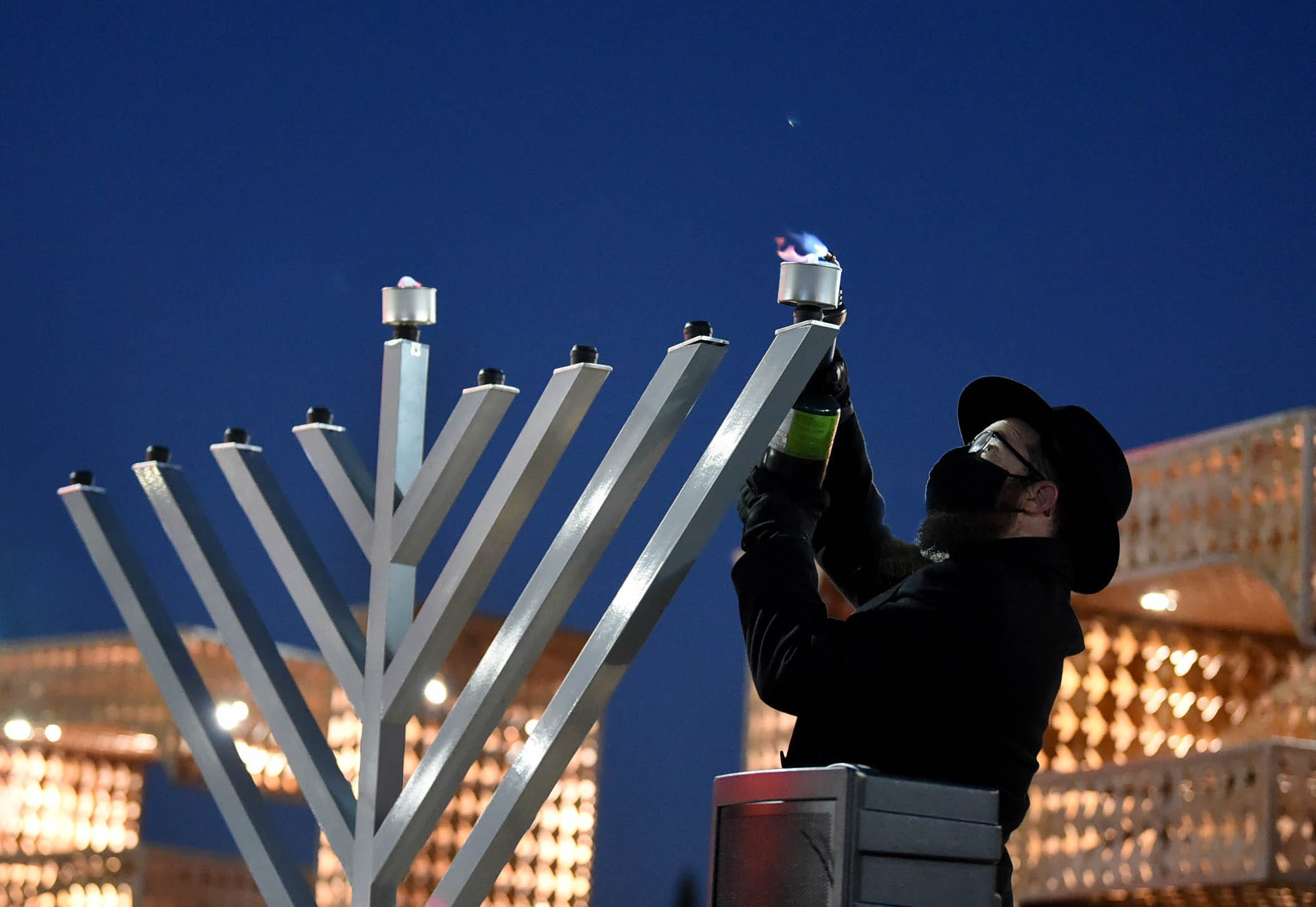 Rabbi Mendel Cunin lights the first candle of the menorah on the first day of Hanukkah during a non-public menorah lighting ceremony on the Reno City Plaza on Thursday Dec. 10, 2020.