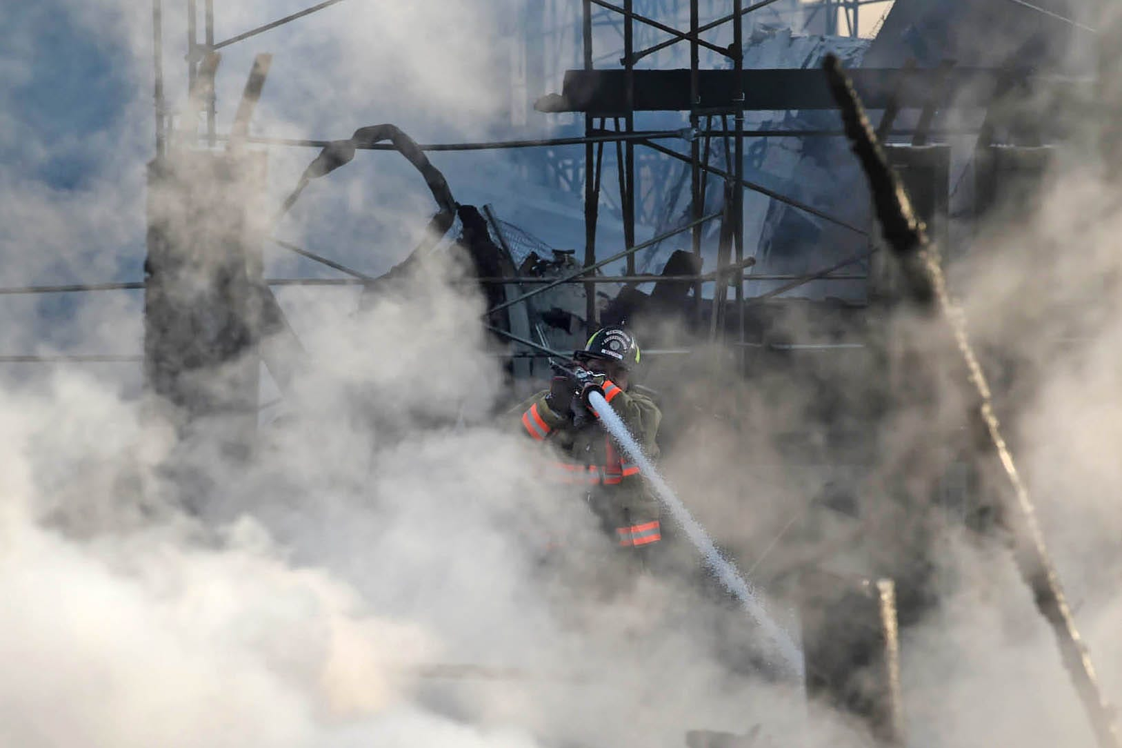 A Reno Firefighter hits a hot spot as they battle fire at a townhome complex under construction in south Reno early in the morning on Thursday July 23, 2020.