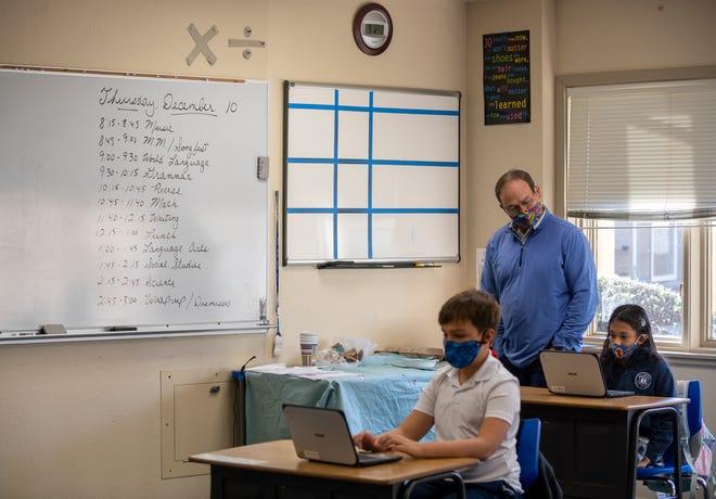 Una maestra lleva puesto un escudo facial en la escuela matutina All Saints ayuda a su alumno durante una lección presencial en Carmel el jueves 10 de diciembre de 2020.