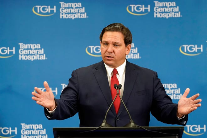 Florida Gov. Ron DeSantis speaks to the media after watching the Pfizer-BioNTech COVID-19 vaccine delivered Monday, Dec. 14, 2020, at Tampa General Hospital in Tampa, Fla. (AP Photo/Chris O'Meara)