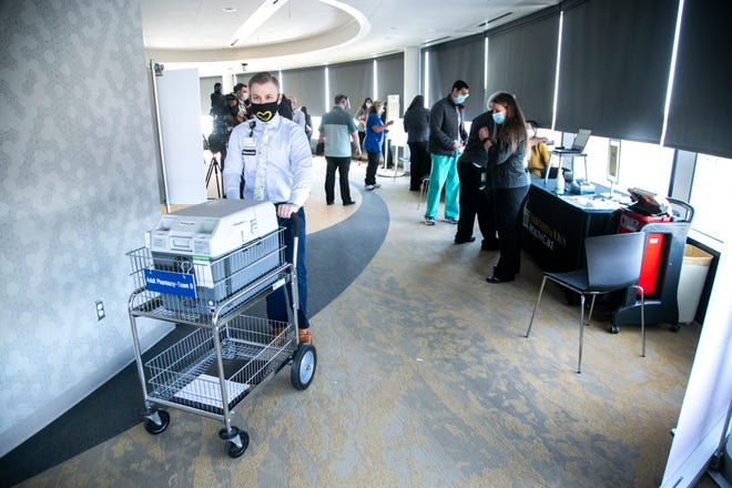 Austin M. Cook, a pharmacy supply chain and automation manager at the University of Iowa Hospitals and Clinics (UIHC), wheels a cart as people receive some of first doses of the Pfizer-BioNTech COVID-19 vaccine at the hospital, Monday, Dec. 14, 2020, on the 12th floor of the University of Iowa Stead Family Children's Hospital in Iowa City, Iowa.  201214 Ia Pfizer Cv Vaccine 007 Jpg